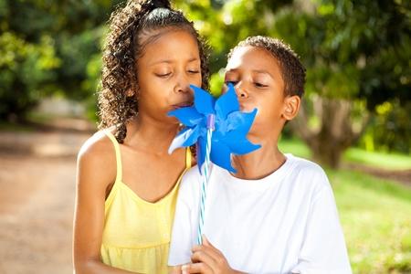 pinwheel: two kids blowing on a pinwheel together Stock Photo