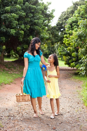 happy mother and daughter walking in fruit garden with basket of apple photo
