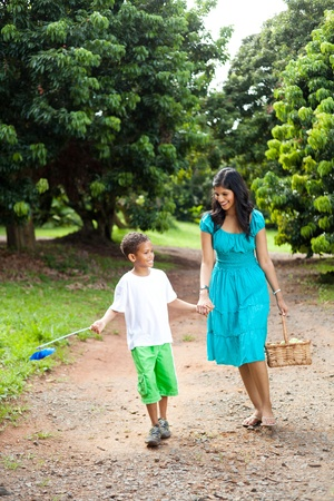 happy mother and son walking in fruit orchard with basket of apple photo