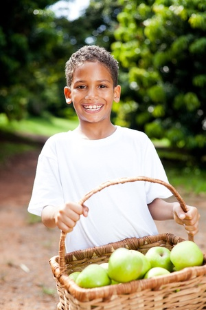 happy little indian boy carrying a basket of apples in orchard photo