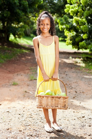 kids dress: happy little girl with basket of apples outdoors in orchard Stock Photo
