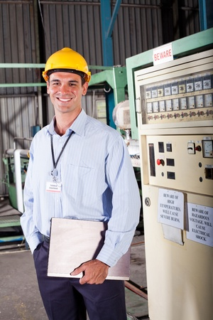 technical department: happy male industrial technician inside a factory