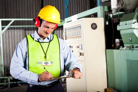 safety helmet: male occupational health and safety officer inside factory doing inspection Stock Photo
