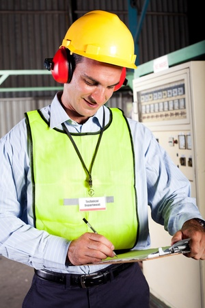 safety hat: male industrial technician working inside a factory Stock Photo