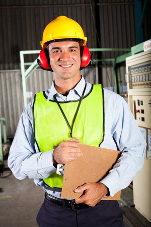 male industrial worker with personal protective equipment inside factory photo
