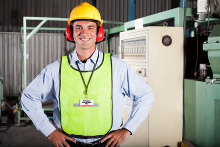 prevention: happy male industrial health and safety officer portrait inside factory