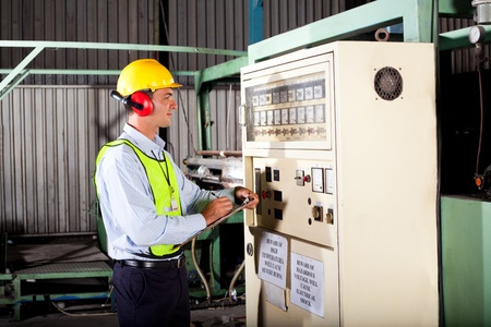 extrusion: male industrial technician writing down machine temperature setting figures