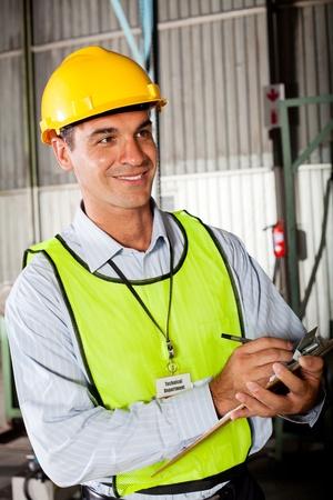 technical department: male caucasian technician taking machine gauge reading Stock Photo