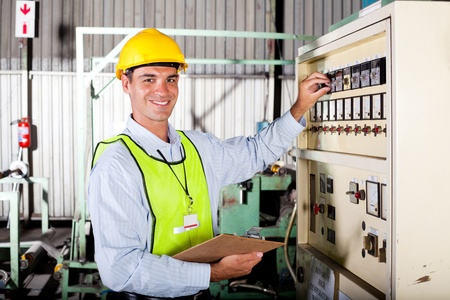 male caucasian technician setting up industrial machine photo
