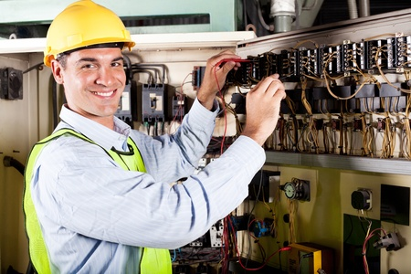 control panel: happy male electrician working on industrial machine Stock Photo