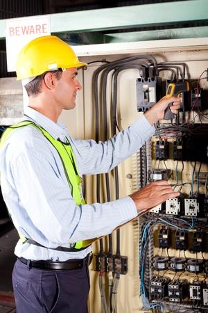 control box: industrial technician checking machine control box temperature