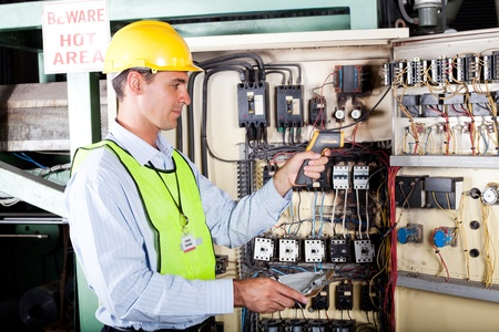 male caucasian electrician checking industrial machine control box temperature photo