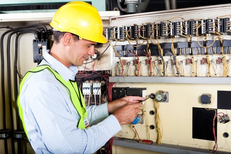 male caucasian electrician changing industrial machine switch