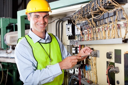 electricidad industrial: t�cnico de feliz hombre cauc�sico reparaci�n de caja de control de la m�quina industrial