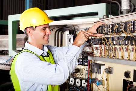 electrical cable: male electrician reapairing industrial machine control component Stock Photo