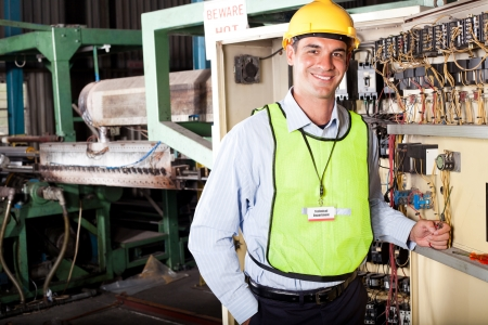 factory worker: male caucasian industrial techincian portrait in front of machinery  Stock Photo