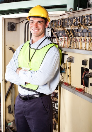 control panel: male caucasian industrial electrician portrait in front of machinery