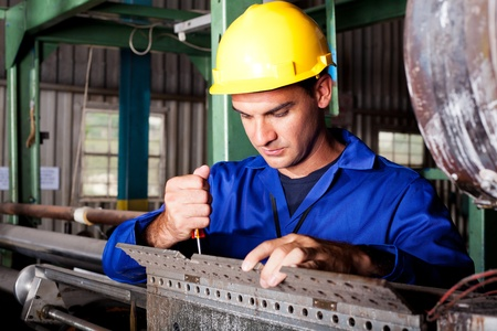 laborers: industrial mechanic repairing heavy industry machine