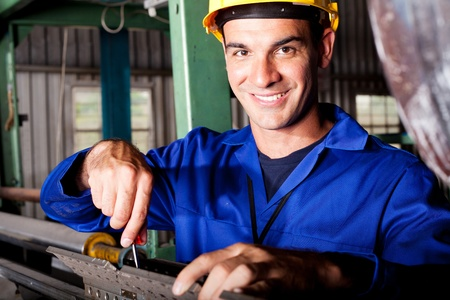 happy caucasian mechanic repairing heavy industry machine photo