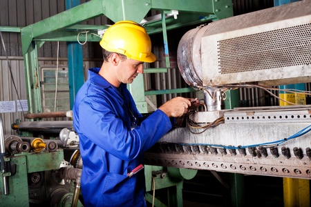 maintenance engineer: industrial mechanic repairing heavy industry machine in plant Stock Photo