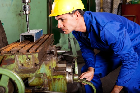 metalwork: professional machinist operating industrial drilling press  Stock Photo