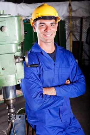 metalwork: portrait of industrial machinist standing next to machine tool