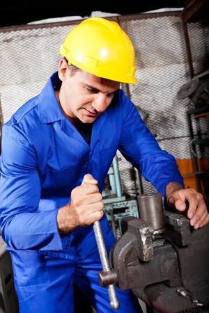 industrial machinist working on vice grip in workshop photo