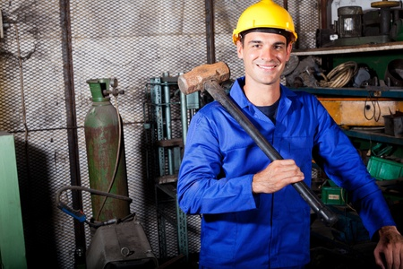 skilled labour: happy male blue collar worker with a big hammer