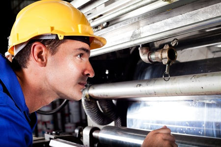 quality check: industrial machine operator checking on machine while it Stock Photo
