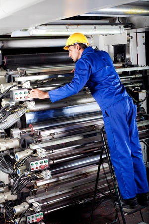 factory worker: modern printing machine operator checking machine