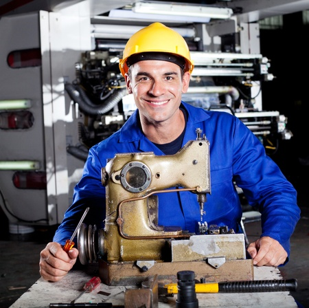 studio happy overall: happy mechanic repairing industrial sewing machine in factory Stock Photo