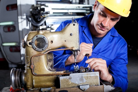 male mechanic reapiring industrial sewing machine in factory photo