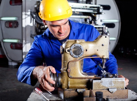 male technician fixing industrial sewing machine in factory photo