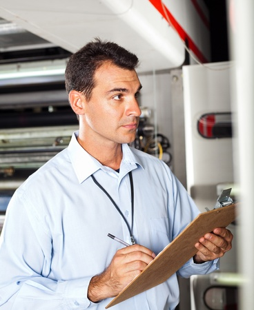 technical department: industrial technician taking machine readings