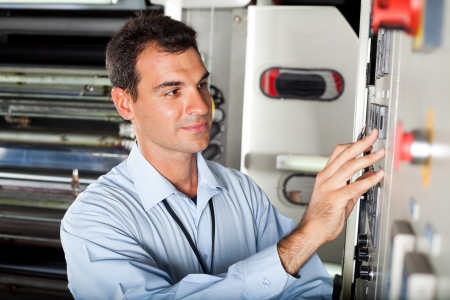 maintenance engineer: male technician setting industrial machine in modern factory