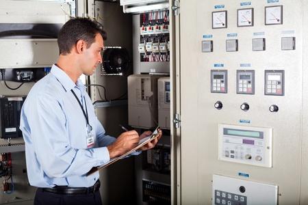 ingenieur electricien: technicien �crire modernes informatis�s contenant des donn�es de r�glage de machine Banque d'images