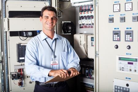 electricidad industrial: retrato de ingeniero industrial en la parte delantera de la maquinaria computarizada