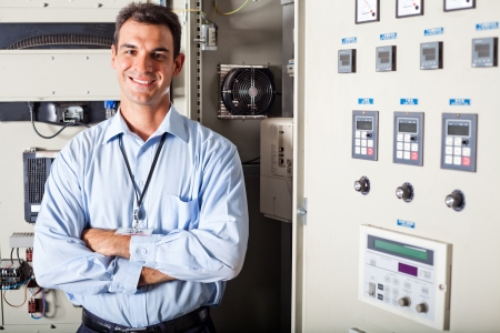 electrical panel: portrait of professional industrial technician in front of computerized machinery