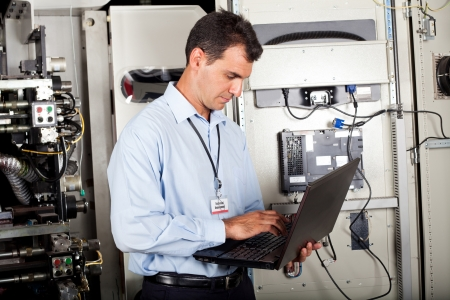 industrial programmer checking computerized machine status with laptop computer photo