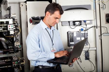 electricista: programador de la industria de comprobar el estado de la máquina computarizada con ordenador portátil Foto de archivo