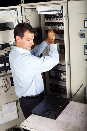 industrial technician repairing computerized machine with laptop computer photo