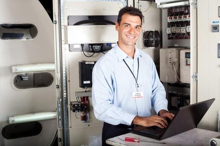 electricista: retrato de técnico industrial profesional frente a la maquinaria Foto de archivo