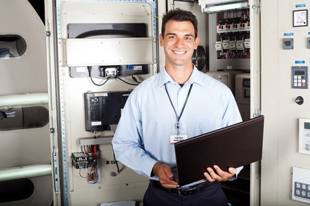 portrait of male industrial engineer in front of machinery photo