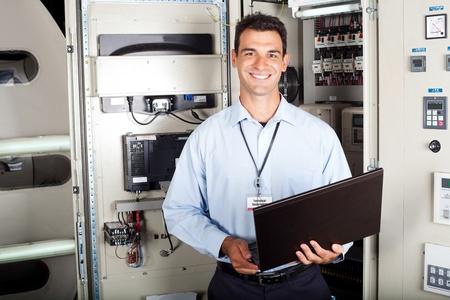 electricista: retrato de ingeniero industrial masculina frente a la maquinaria