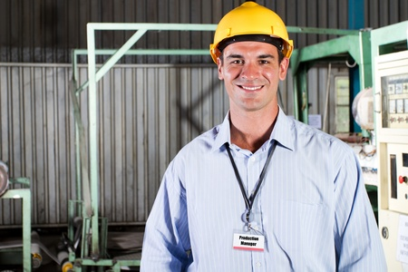 steel worker: happy male production manager portrait inside factory