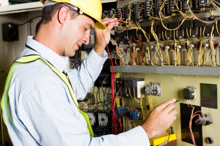 electricity meter: male caucasian electrician testing industrial machine Stock Photo
