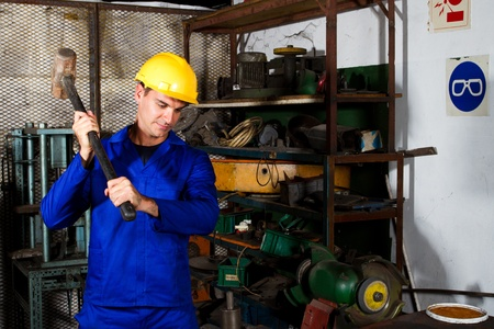 factory blue collar worker using big hammer in workshop Stock Photo - 12430919