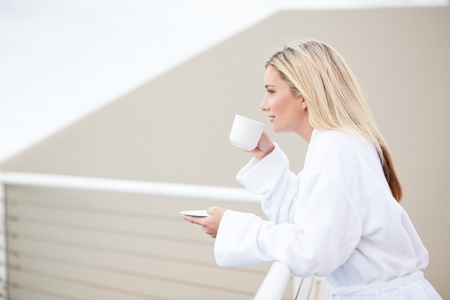 young woman in bathrobe drinking coffee on balcony in the morning photo