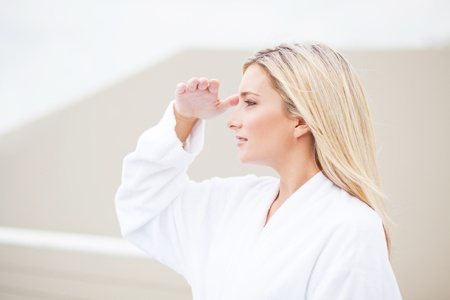 attractive young woman in bathrobe and looking into the distance photo