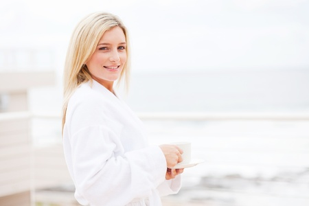 attractive young woman in bathrobe drinking coffee in the morning photo